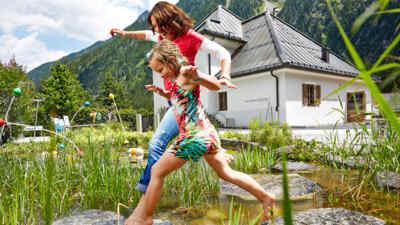 Kind und Frau springen über Steine