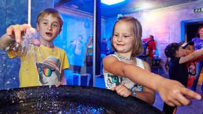 Zwei Kinder testen die Ausstellungsobjekte